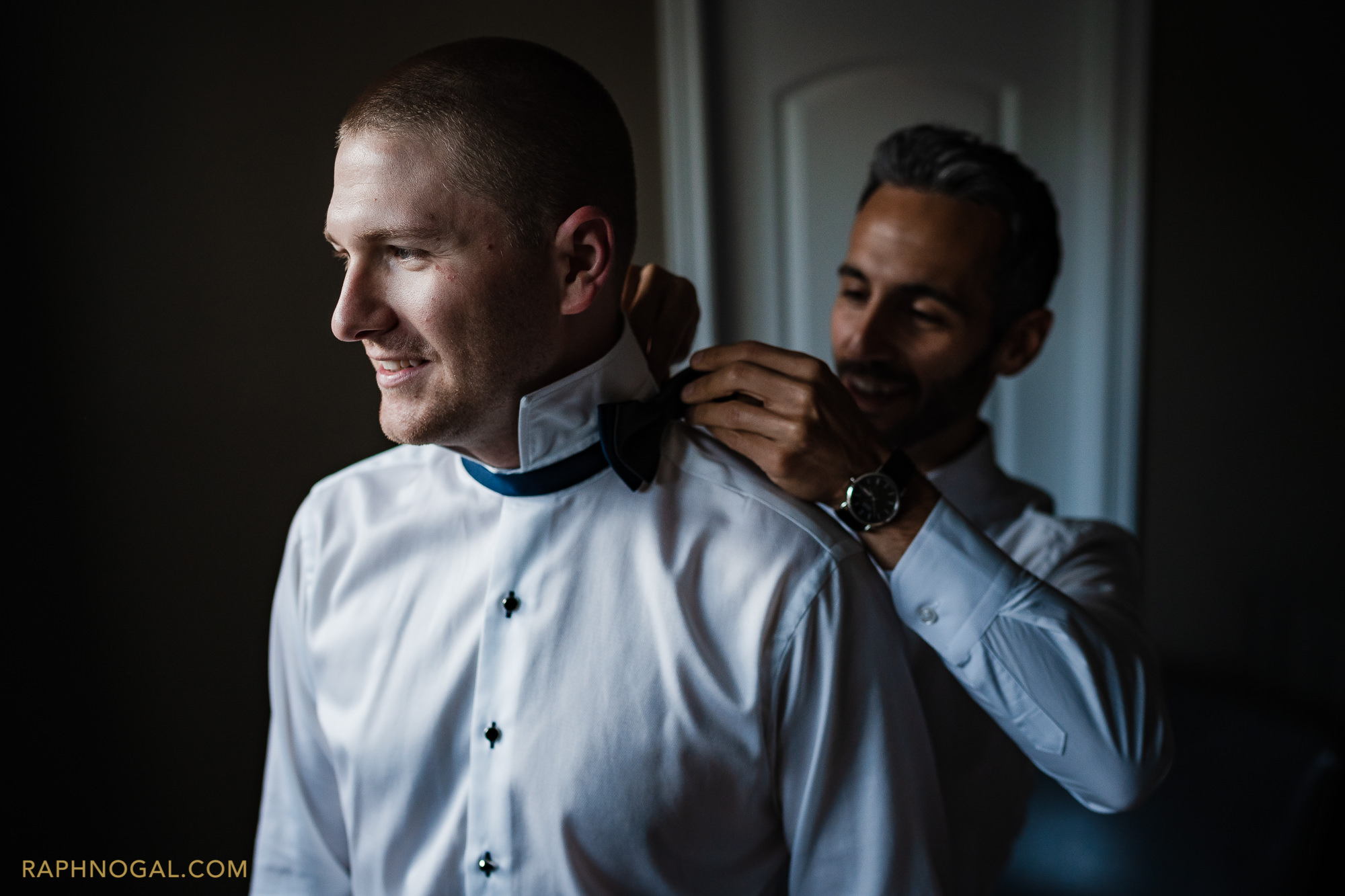 groom getting bow tie put on by best man