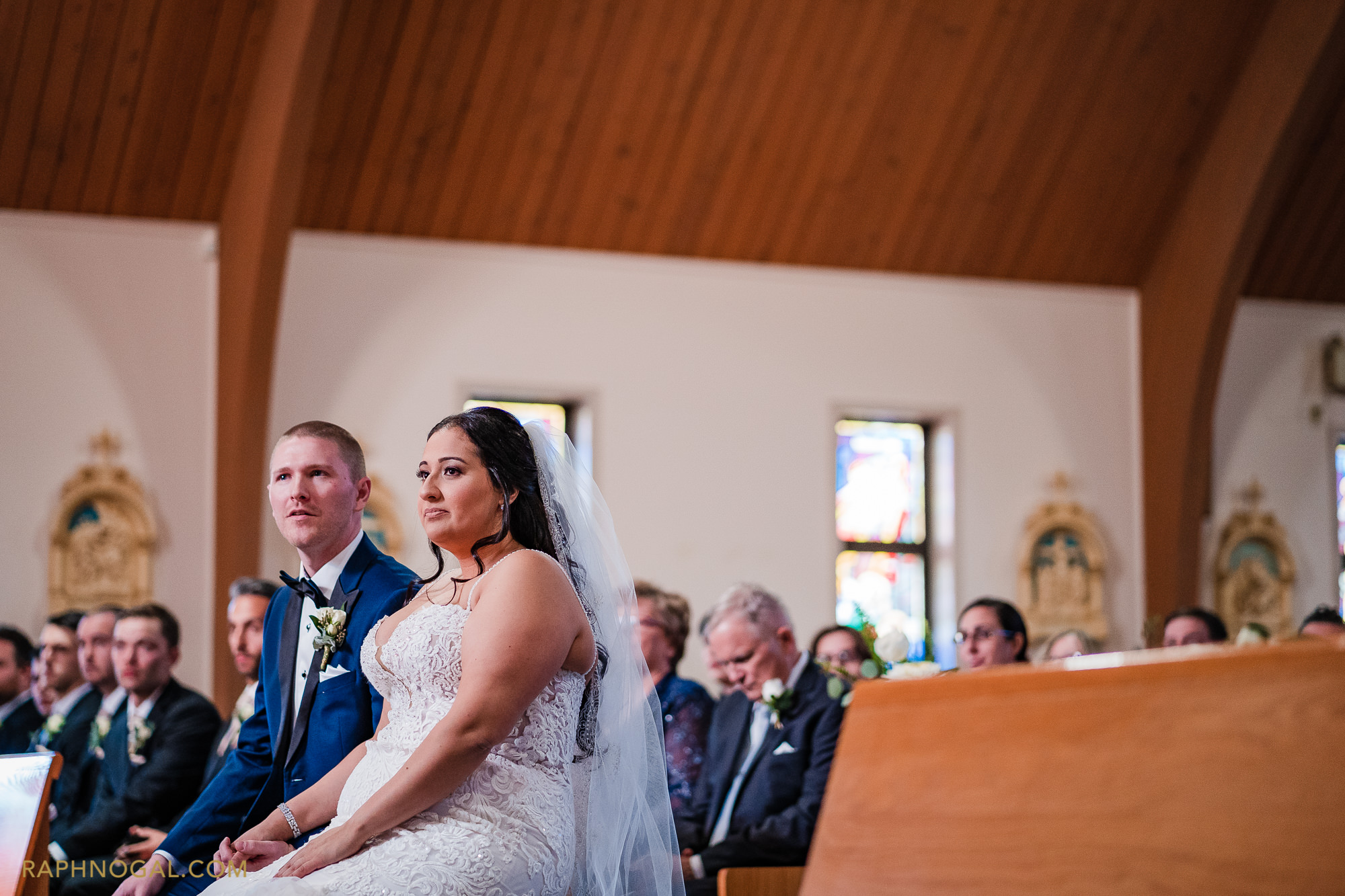 Bride and Groom sit at church listening to priest
