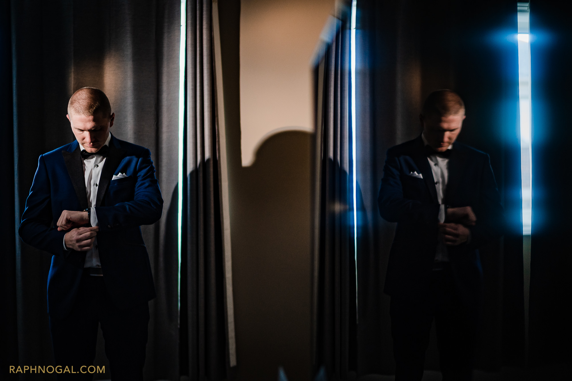 Groom putting on cufflinks, reflected in a TV screen
