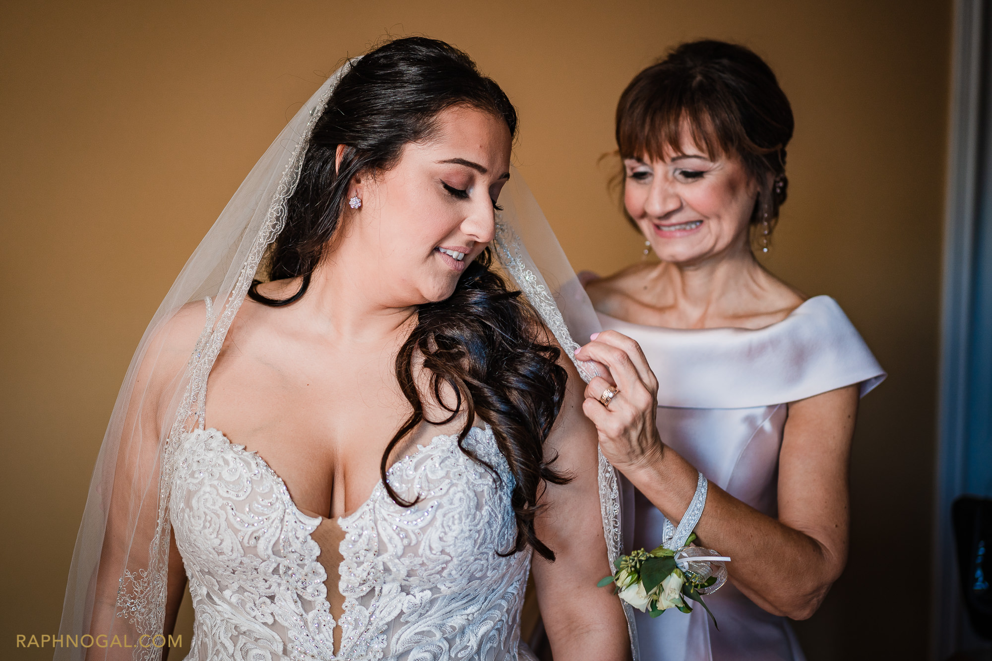 Bride's mother helping bride put on the veil
