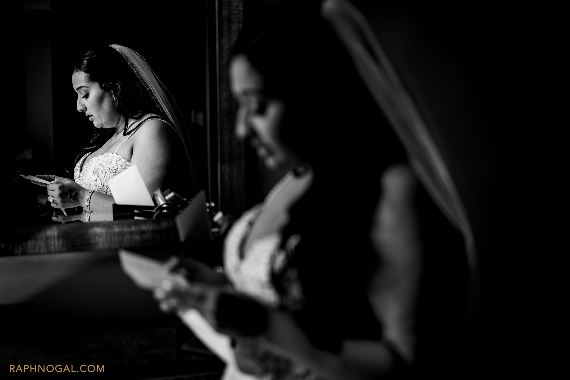 Bride reading card, reflected in the mirror