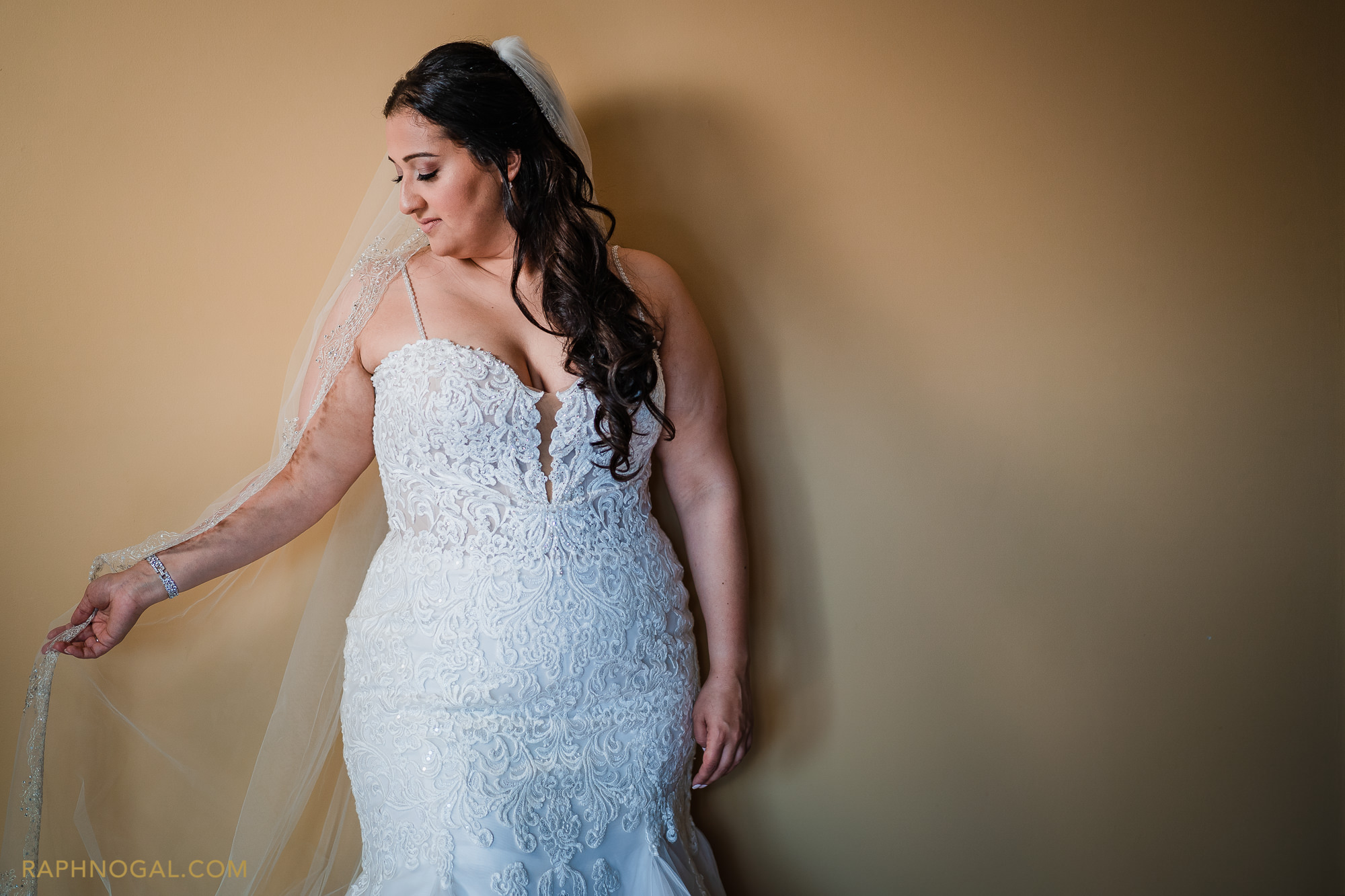 Bride playing with veil against yellow wall