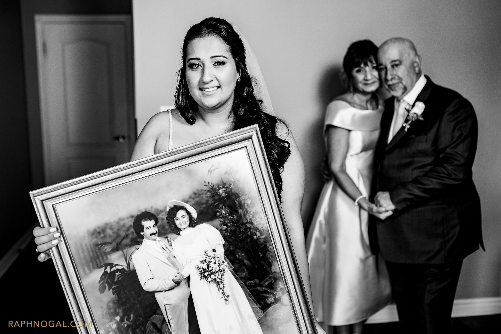 Bride holding photo of parents' wedding day